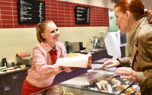 Verkäuferin im Supermarkt an der Käsetheke bedient Kundin // Saleswoman in the supermarket serves customer